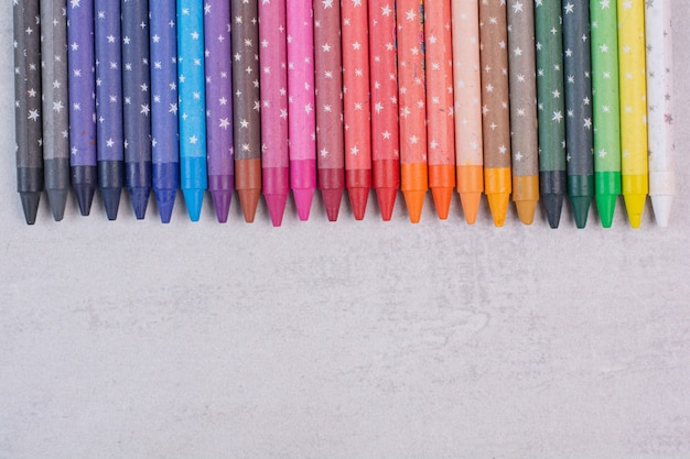 Montón de lápices de colores sobre superficie blanca