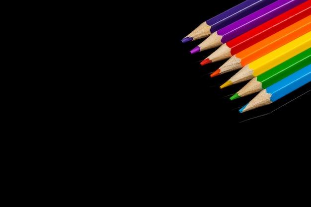Un montón de lápices de colores variados con copyspace sobre vidrio negro