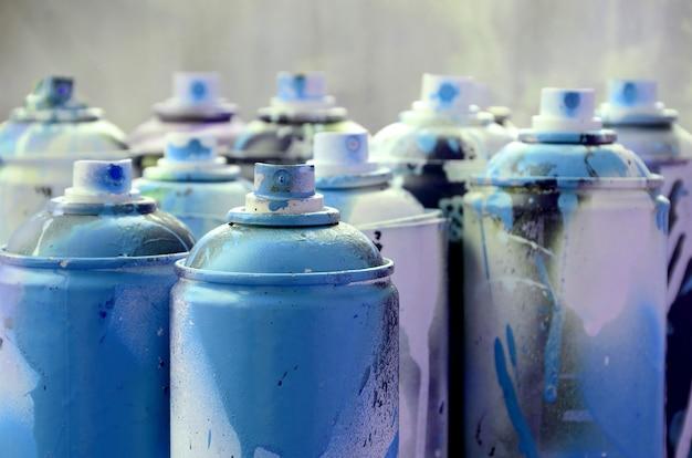 Un montón de latas de aerosol sucias y usadas de pintura azul brillante.