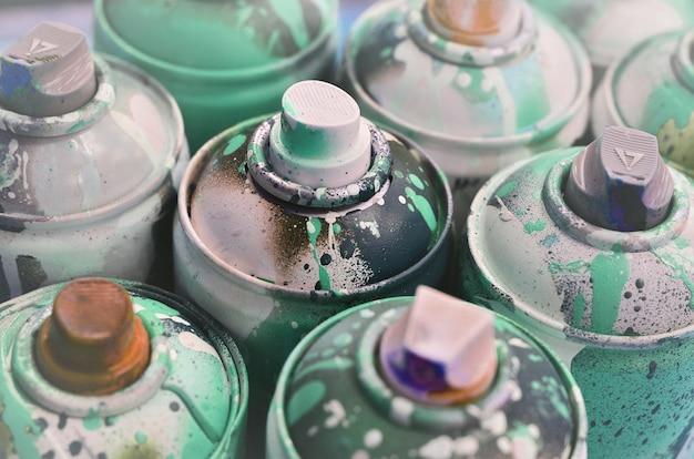 Un montón de latas de aerosol usados de pintura de primer plano. latas sucias y manchadas para dibujar graffiti.