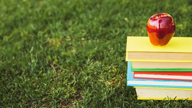 Montón de libros brillantes con manzana encima en césped verde