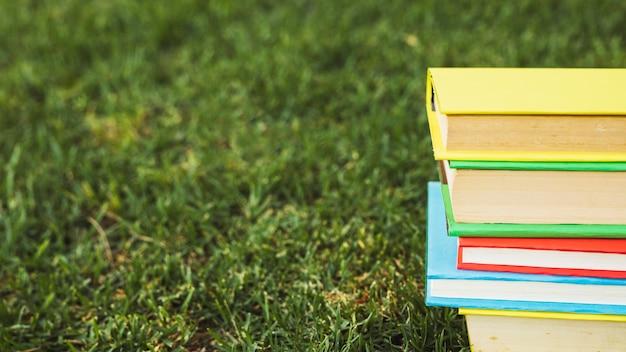 Montón de libros con cubiertas de colores en césped verde