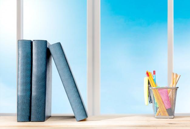 Montón de libros de pie y lápices en el contenedor de la cesta con grapadora verde sobre la mesa de madera