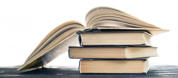 Montón de libros raros. libro abierto, libros de tapa dura en la mesa de madera.