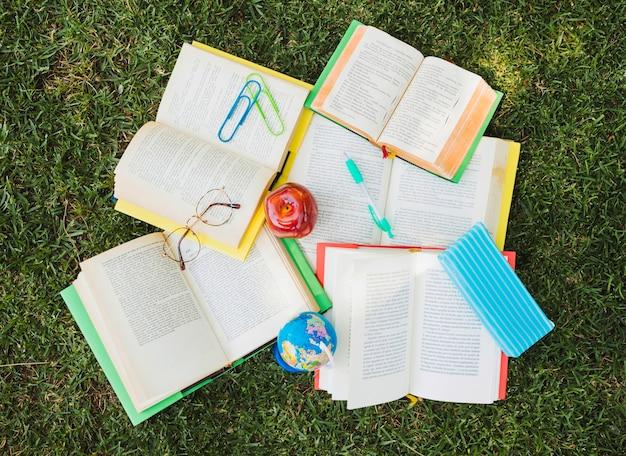 Montón de libros de texto con papelería en caos en césped verde