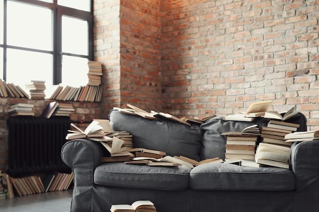 Un montón de libros tumbados en el sofá. nadie