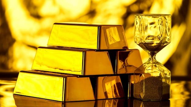 Montón de lingotes de oro brillante y reloj de arena sobre la mesa.