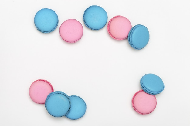Montón de macarrones dulces de primer plano de color azul y rosa sobre un fondo blanco. galletas con aroma a lavanda. copia espacio