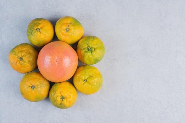 Montón de mandarinas alrededor de pomelo sobre fondo gris.