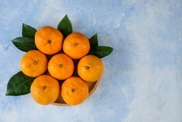 Montón de mandarinas clementinas y hojas sobre placa de madera