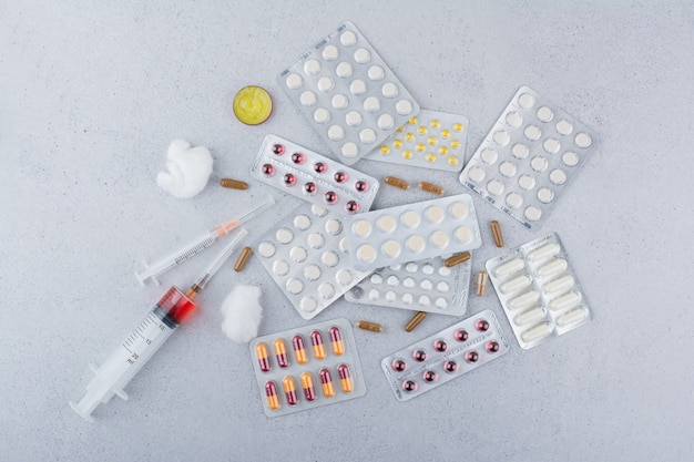 Montón de medicamentos, píldoras, cápsulas y jeringas.