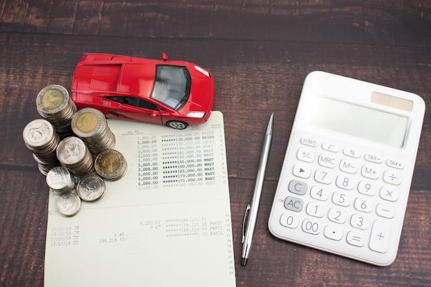 Montón de monedas, bolígrafo negro, calculadora y carro rojo en papel. aumento del gasto en compras de automóviles.