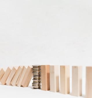 Montón de monedas deteniendo piezas de madera caídas