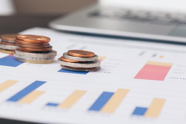 Montón de monedas de dinero con papel cuadriculado en mesa de madera, en cuenta, finanzas y crecimiento del negocio