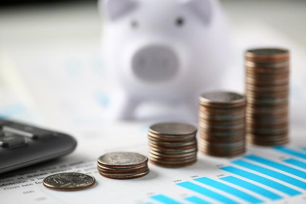 Montón de monedas de plata y hucha blanca stand en documentos financieros