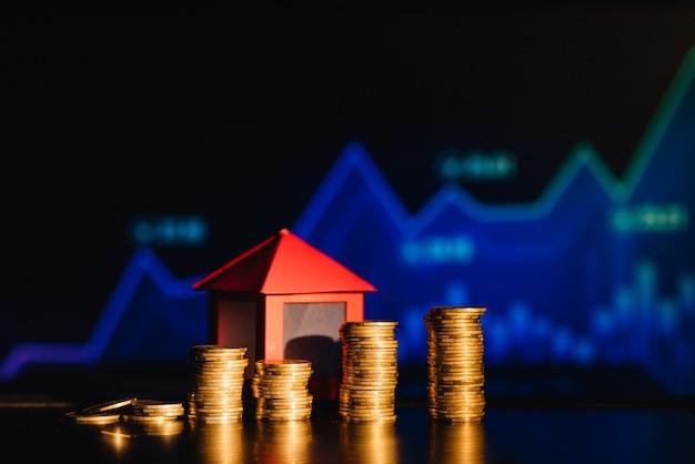 Un montón de monedas proyectando una sombra como casa, concepto de ahorro