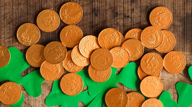 Montón de monedas y tréboles de papel en mesa de madera