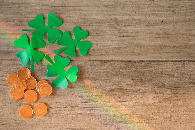 Montón de monedas y tréboles de papel verde a bordo