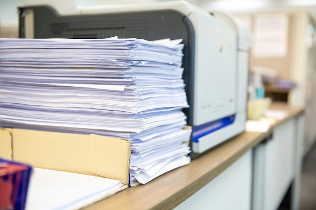 Montón de un montón de papel se apila en la oficina de escritorio