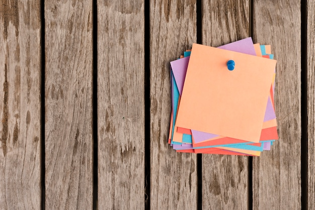 Montón de notas adhesivas adjuntas con alfiler azul en la mesa de madera
