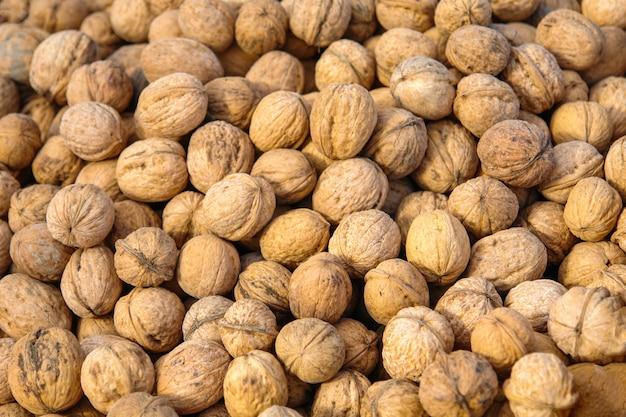 Un montón de nueces con cáscara en el mostrador del mercado
