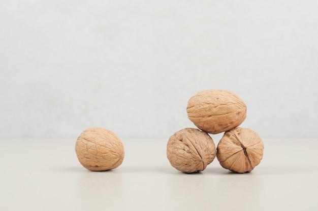 Montón de nueces orgánicas sobre superficie beige