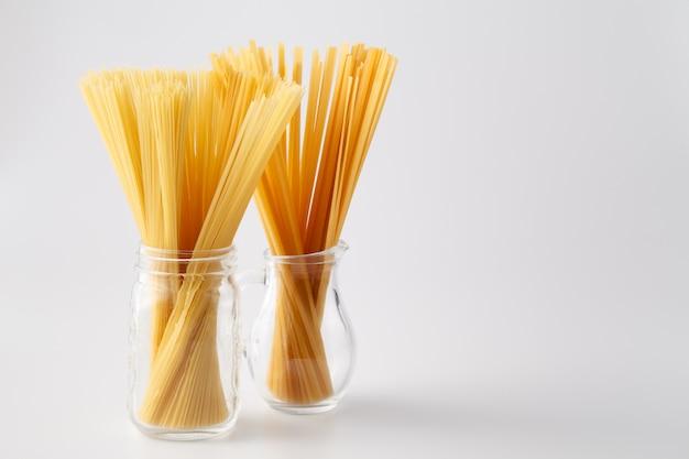 Montón de pasta italiana cruda en frasco de vidrio sobre superficie blanca