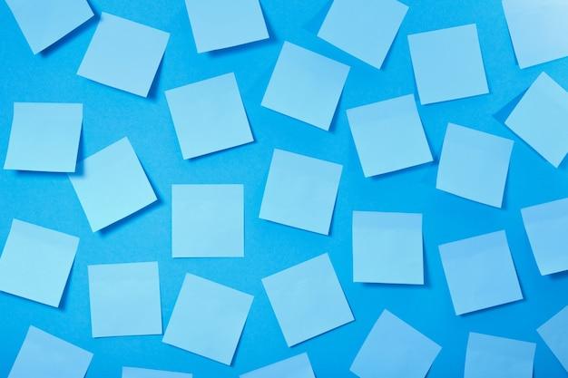 Un montón de pegatinas de papel de color azul claro sobre un fondo azul, un patrón de pegatinas para notas