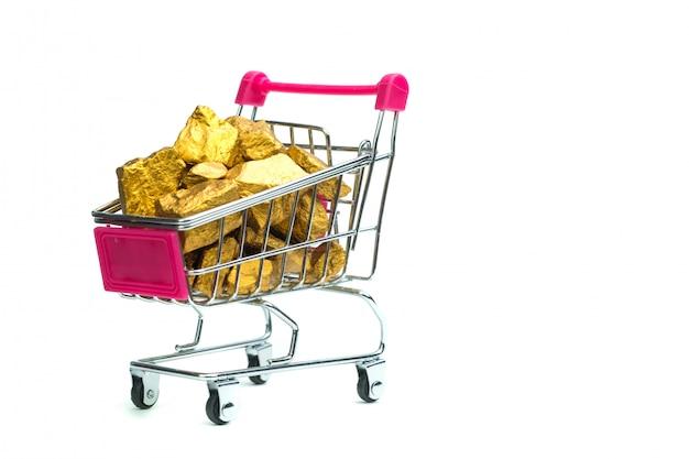 Montón de pepitas de oro o mineral de oro en carrito de la compra.