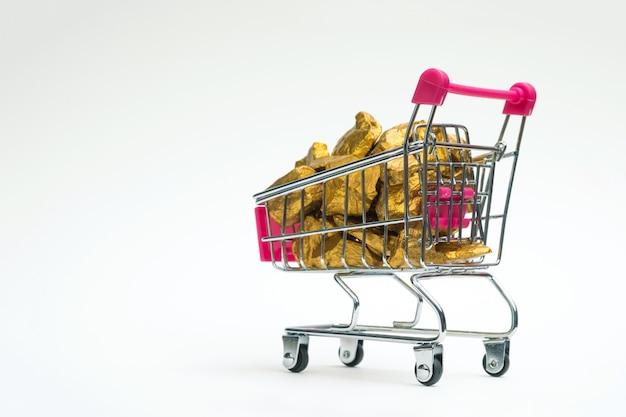 Montón de pepitas de oro o mineral de oro en el carrito de compras o en el carrito de supermercado