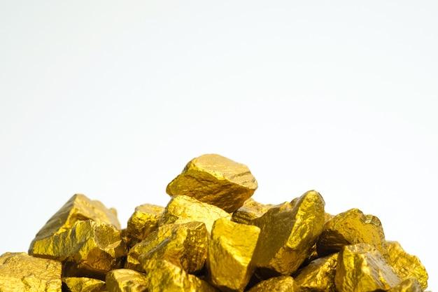 Un montón de pepitas de oro o mineral de oro sobre fondo blanco.