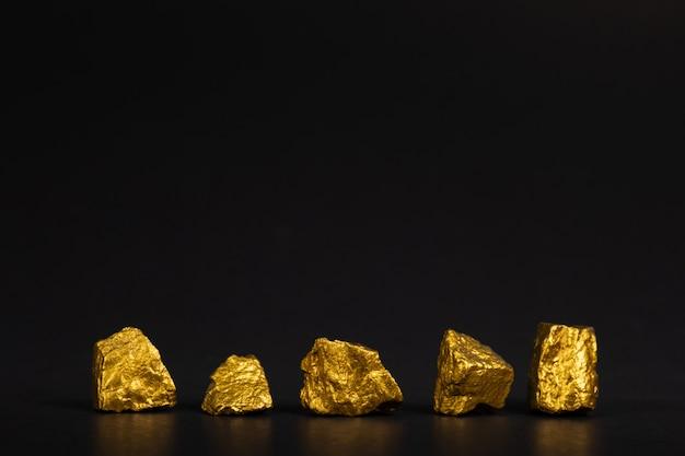 Un montón de pepitas de oro o mineral de oro sobre fondo negro