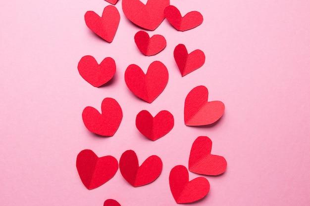 Un montón de pequeños corazones de color rojo contra un fondo rosa. feliz día de san valentín.