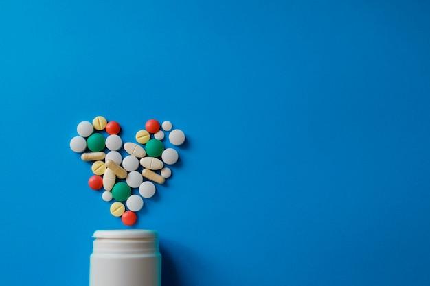 Montón de píldoras en azul surtido de píldoras de medicina farmacéutica, tabletas y cápsulas y botella en azul