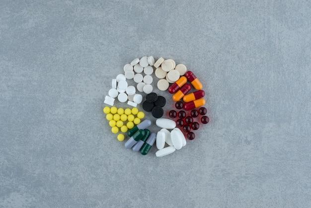 Un montón de píldoras de colores médicos sobre superficie gris