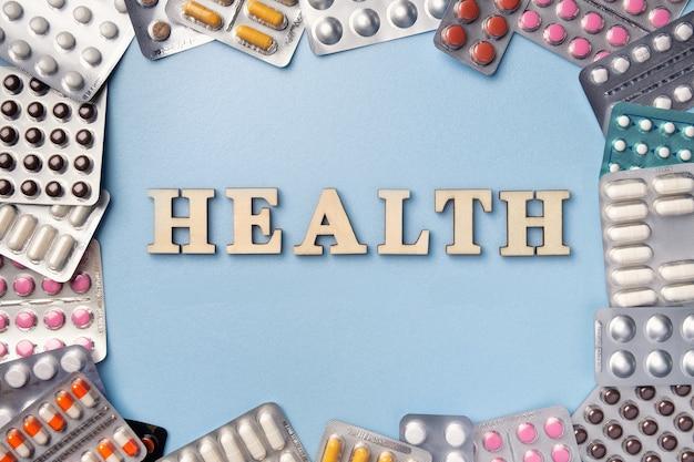 Montón de píldoras de diferentes colores en blisters pack sobre fondo azul con texto e inscripción salud de letras de madera, espacio de copia. tabletas de farmacia para tratamiento.