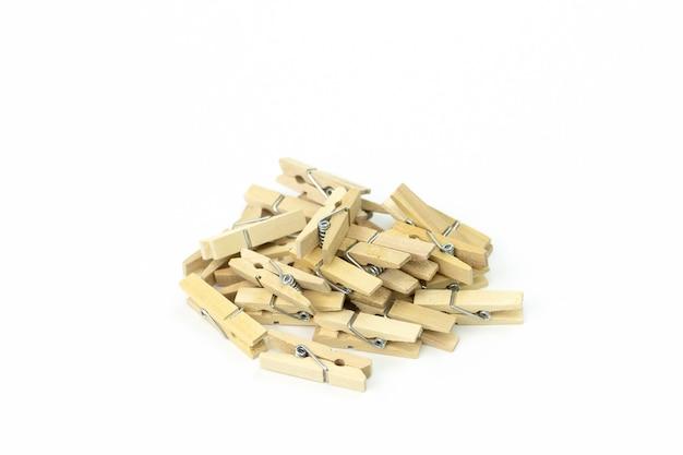 Montón de pinzas de madera apiladas en desorden sobre superficie blanca