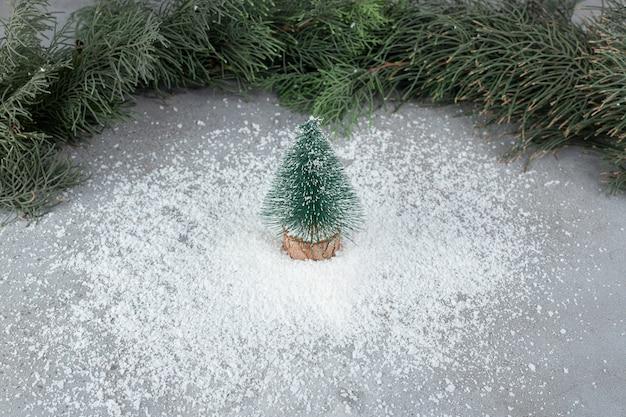 Montón de polvo de coco debajo de la figura del árbol, frente a las ramas de pino en la superficie de mármol