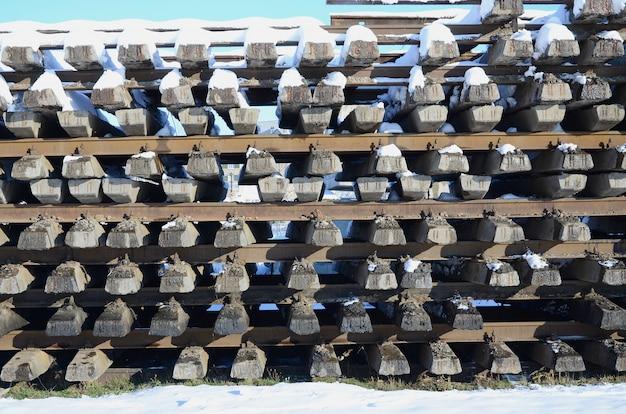 Un montón de rieles viejos y traviesas se apilan en un almacén ferroviario en invierno.
