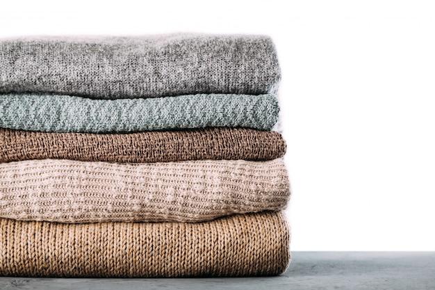 Montón de ropa de invierno tejida en la mesa