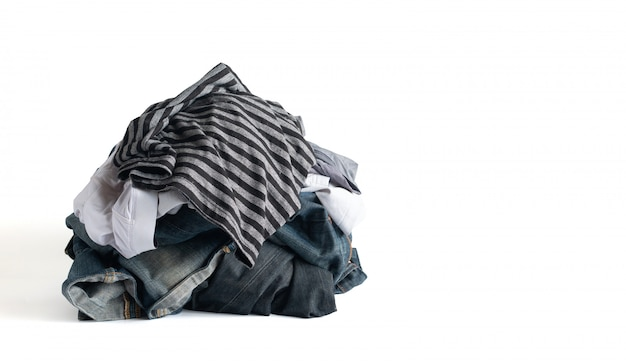 Un montón de ropa y pantalones vaqueros desteñidos aislado sobre fondo blanco con trazado de recorte