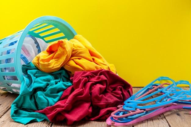 Montón de ropa sucia en la cesta de lavado sobre tabla de madera.