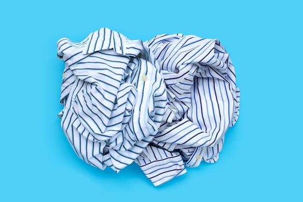 Montón de ropa usada en superficie azul