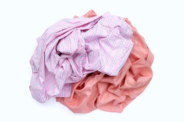 Montón de ropa usada en superficie blanca