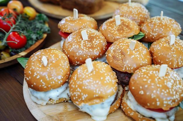Un montón de sabrosas hamburguesas en la mesa de madera
