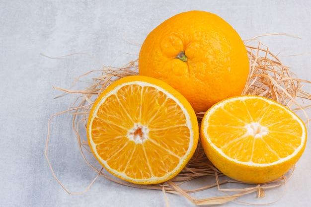 Un montón de sabrosas naranjas sobre una pajita, sobre la mesa de mármol.