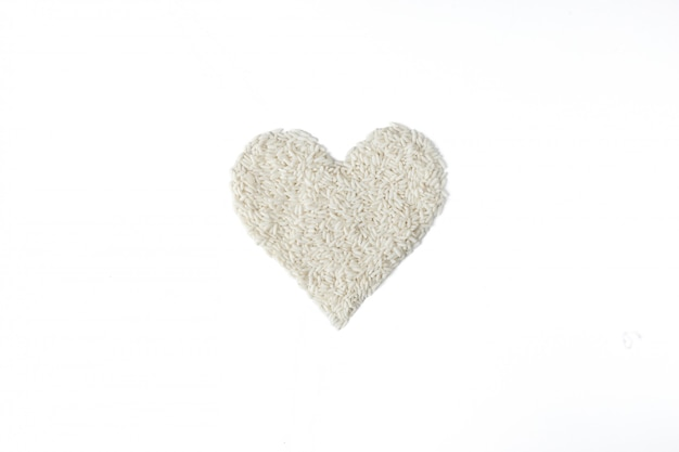 Montón de semillas de arroz en forma de corazón aislado sobre fondo blanco.