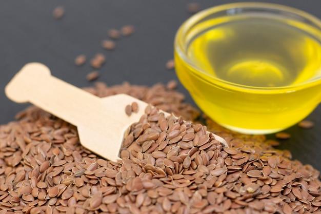 Un montón de semillas de lino y aceite de lino en una cuchara de madera sobre un fondo de piedra negra.