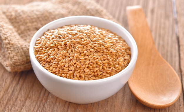 Montón de semillas de lino en un tazón sobre una tabla