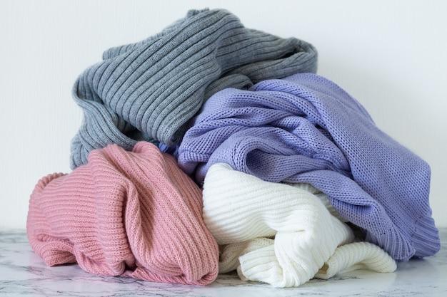 Montón de suéteres calientes en la mesa de mármol.